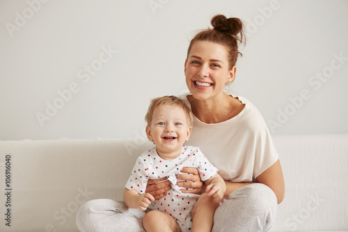 Fotografie, Obraz  Charming brunette woman playing with her baby while sitting on a bed in her apartment at the weekend together, lazy morning, warm and cozy scene