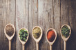 Aromatic herbs and spices on wooden spoons