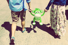 Cropped Rear View Of Couple Holding Hands With Inflatable Monkey
