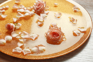 Obraz na płótnie Canvas Pink rose petals in golden bowl with water on wooden background