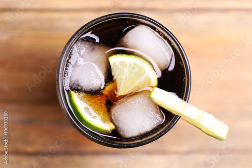Fototapeta Cocktail with lime slices and ice blocks on wooden table, top view obraz na płótnie