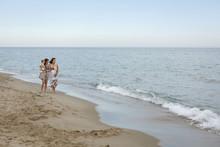 Women Walking Along Shore With...