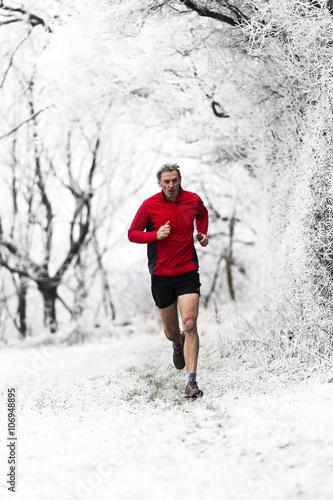 Fotobehang Wintersporten Man running through woods in winter, Wenlock Edge, Shropshire, England, UK