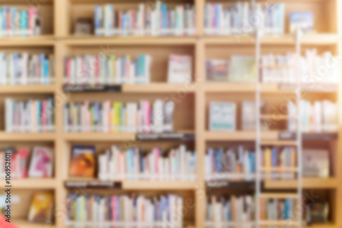 Photo  blurred bookshelf in library room for your background design