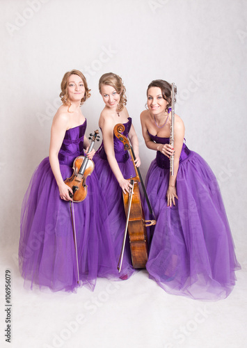 Fotografering  musical trio in purple dresses