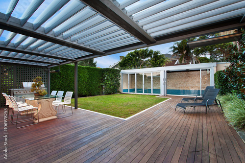 a beautiful courtyard with a lawn and swimming pool Fototapeta