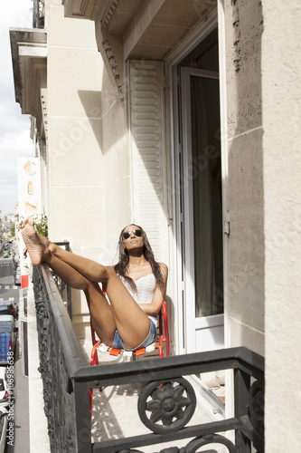 Woman sunning on balcony, Paris, France