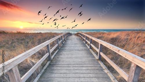 Zdjęcie XXL długa, drewniana droga do morza - zachód słońca nad Morzem Bałtyckim