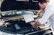 Man using a laptop to detect malfunction in the car