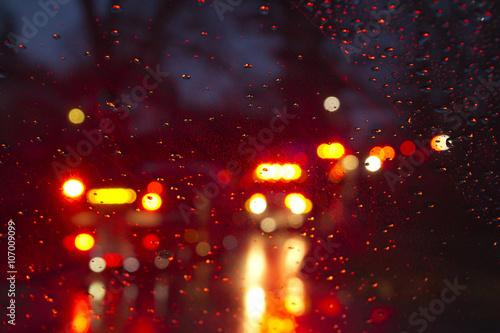 Cuadros en Lienzo  Emergency Vehicles Flashing Through a Wet Windshield Darkly