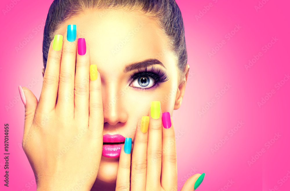 Fototapeta Beauty girl face with colorful nail polish