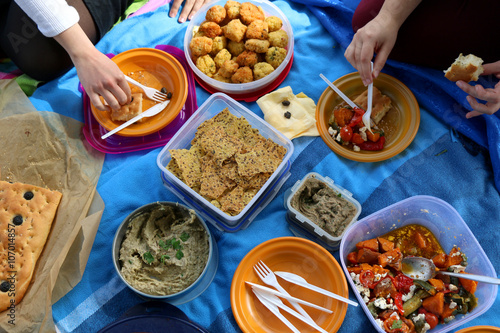 Fotoposter Picknick Top view of various picnic food: vegetable and feta salad, baba ghanoush, healthy crackers, rice fritters and olive bread.