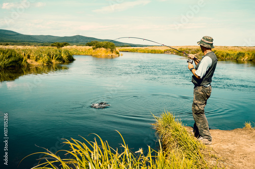 Keuken foto achterwand Vissen Middle aged man fishes caught pink salmon from the river
