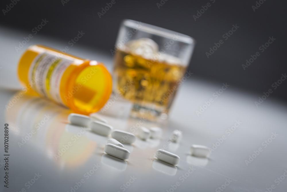 Fototapeta Prescription Drugs Spilled From Fallen Bottle Near Glass of Alco