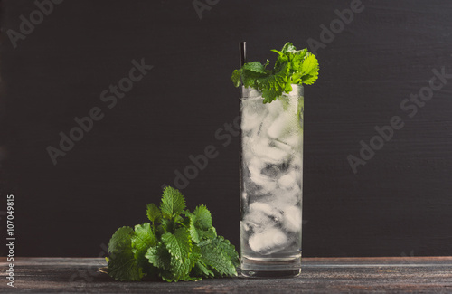 Valokuva  Mint julep in glass on the dark wooden background. Toned image.