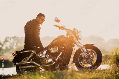 Fotografering  young brutal man in a black jacket and glasses standing near a motorcycle
