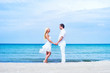 Loving couple walking and embracing on a summer beach