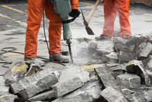 Workers At Construction Site Demolishing Asphalt