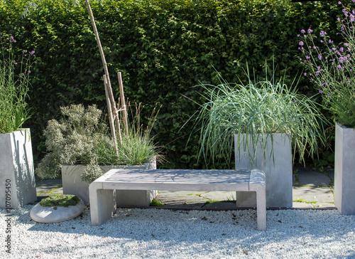 Fotografie, Obraz  Trädgårdsbänk i en dekorerad och lummig trädgård