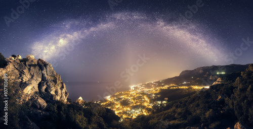 Spoed Foto op Canvas Zwart Beautiful night landscape with Milky Way against city lights
