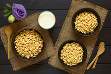 Honey Flavored Breakfast Cereal In Three Rustic Bowls With A Glass Of Milk And Wooden Spoons On The Side, Photographed Overhead On Dark Wood With Natural Light