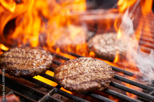 Aluminium Prints Grill / Barbecue hamburgers and hot dogs cooking on grill with flames