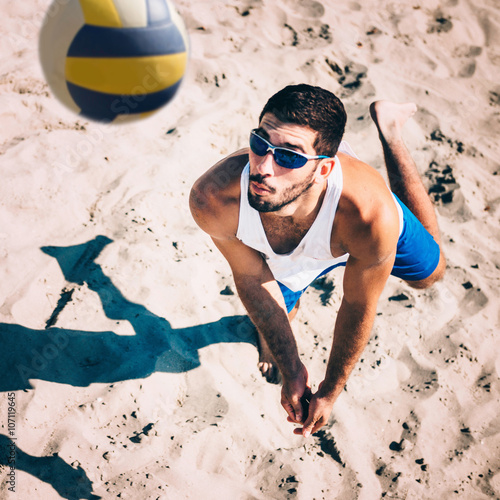 Beach volleyball male player in action, receiving the ball