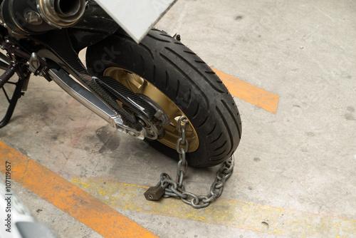 padlock security lock blocking the motorcycle wheel on street Canvas Print