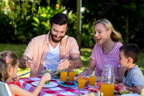Photo  Family enjoying breakfast at table in yard
