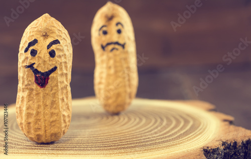 Smile and sad face drawn on dried peanuts on wooden