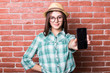 Beautiful young dark-haired girl in casual clothes, hat and eyeglasses posing, smiling and demonstrate on smartphone, standing against brick wall