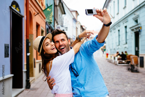 Happy couple taking selfie on the street during vacation in Euro Wallpaper Mural