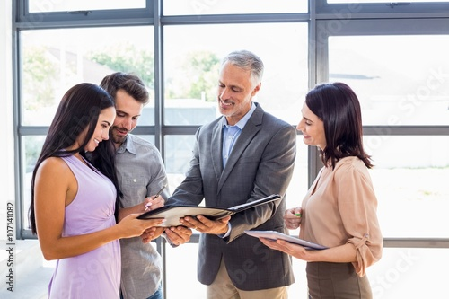 Real estate agent handing over agreement paper to couple Canvas Print