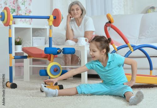little granddaughter doing exercise - 107144016