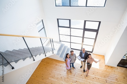 Photo  Real estate agent showing new house to couple