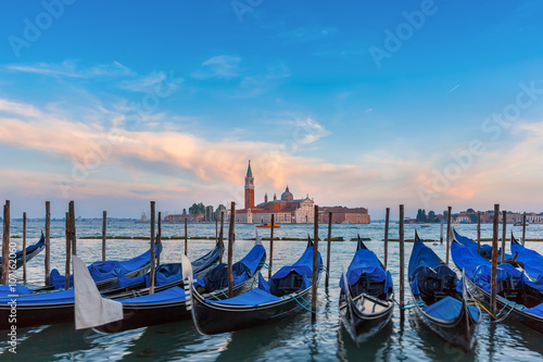 Fotografering  Gondolas moored by Saint Mark square with San Giorgio di Maggiore church in the