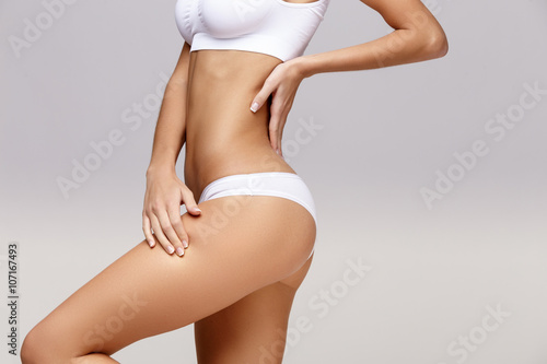 Foto Slim tanned woman's body over gray background
