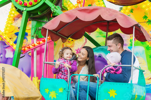 Father, mother, daughters enjoying fun fair ride, amusement park