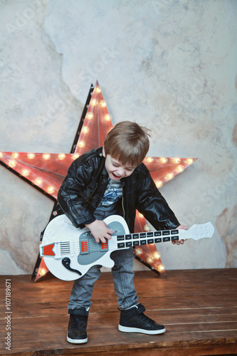 Fotografie, Obraz  little cute 4 years boy playing guitar and singing like a rock-star