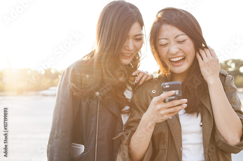 Fotografía  Two young women are laughing to see the smartphone together