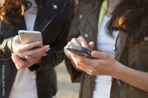 Fotografie, Tablou  Two young women are each other to show the smartphone