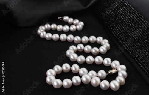 Fotografia Pearl necklace on black jacket