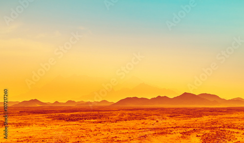Poster Melon African landscape, hot climate in stone desert with silhouettes of hills on the horizon.