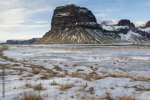 фотография  Landscape with snow covered grass and Lomagnupur mountain, Iceland