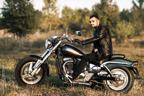 young brutal man in a black jacket and glasses sits near a motorcycle Slika na platnu