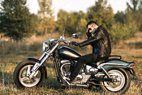 Foto  young brutal man in a black jacket and glasses sits near a motorcycle