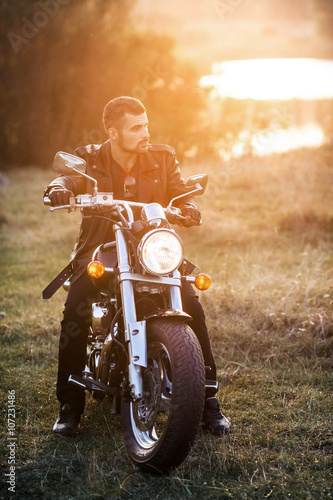 Photo  young brutal man in a black jacket and glasses sits near a motorcycle