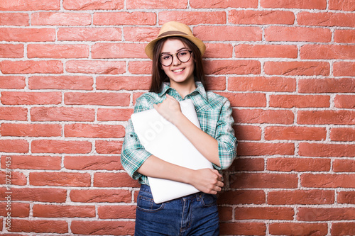 Valokuva  Beautiful young dark-haired girl in casual clothes, hat and eyeglasses posing,