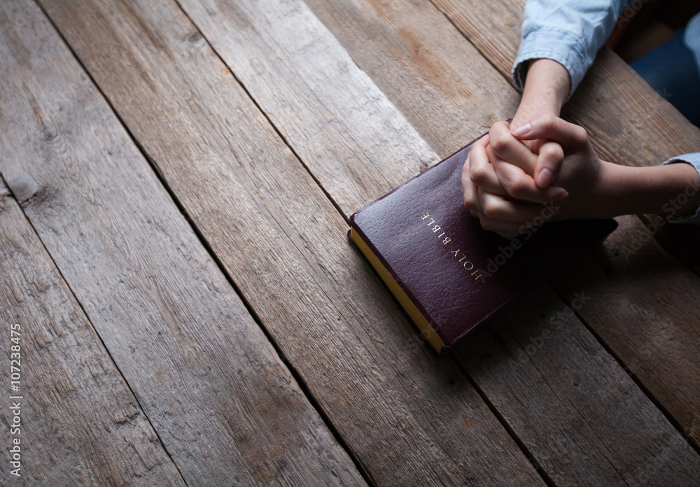Fototapety, obrazy: hands praying with a bible in a dark over wooden table