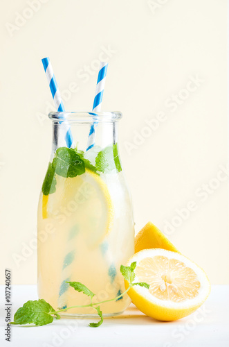 Photo  Bottle of homemade lemonade with mint, ice, lemons, paper straws and pastel blue